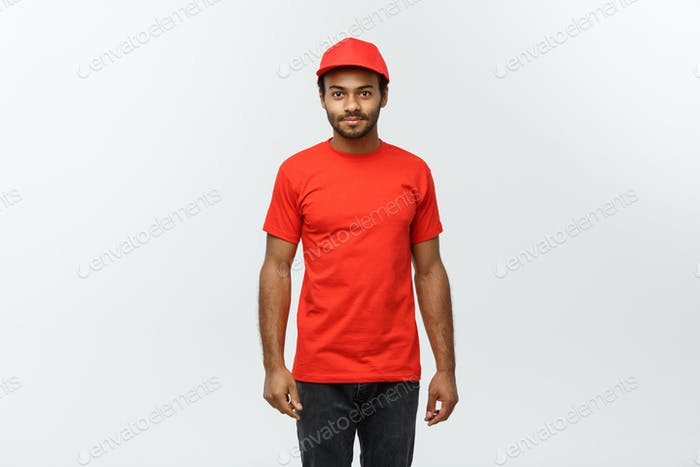Delivery Concept - Handsome African American delivery man. Isolated on Grey studio Background. Copy