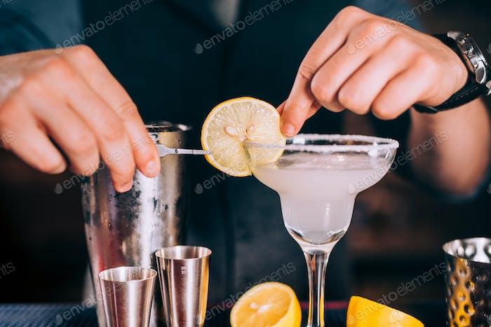 Close up of barman hands preparing margarita cocktail in fancy glass at nightclub