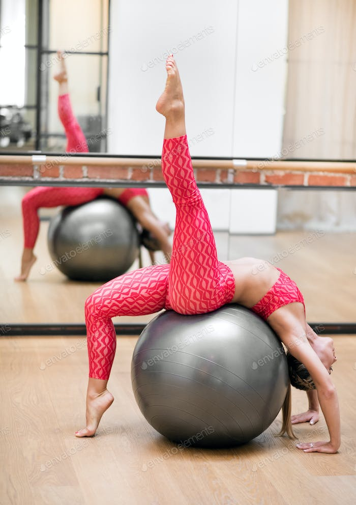 Woman exercising on a stability ball in a gym