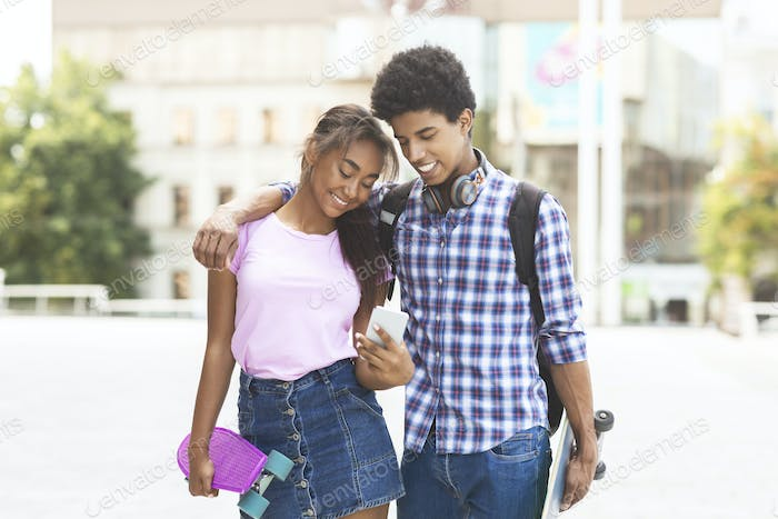 Happy african american couple using smartphone while walking outdoors