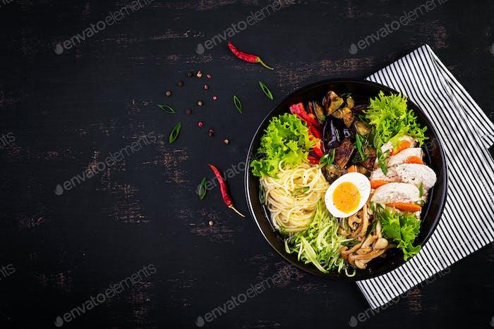 Japanische Ramensuppe mit Huhn, Ei, Shimeji Pilzen und Auberginen auf dunklem Holzhintergrund.