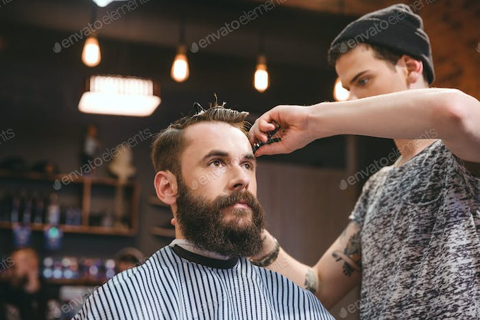 Skillful barber cutting hair of young man with beard