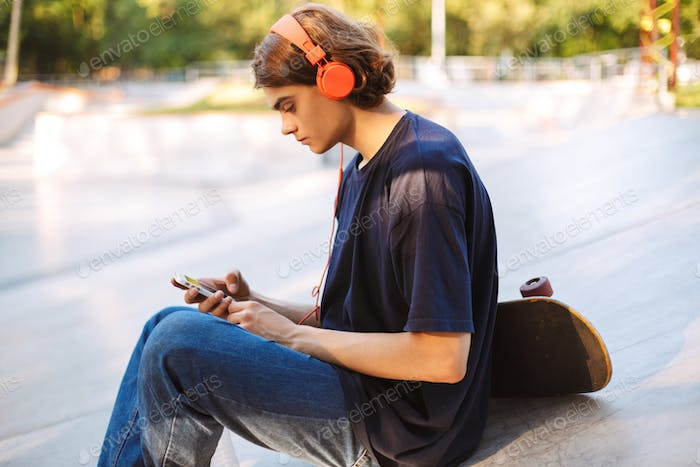 Young skater in orange headphones thoughtfully using cellphone w