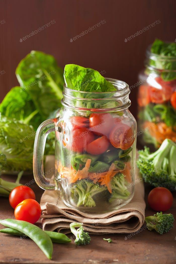 healthy vegetable salad in mason jar. tomato broccoli carrot pea