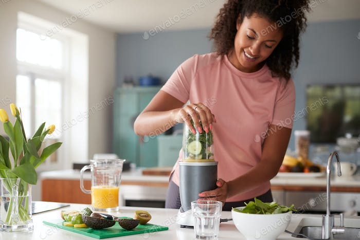 Woman Making Healthy Juice Drink With Fresh Ingredients In Electric Juicer After Exercise