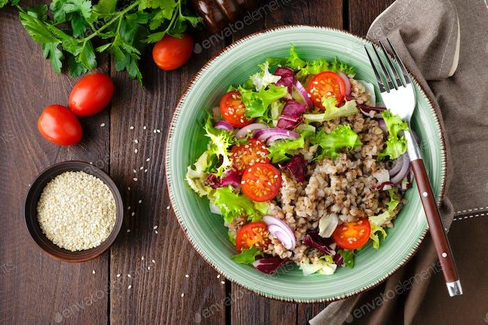 Fresh vegetable salad with lettuce, onion, tomatoes and buckwheat porridge. Healthy vegan food