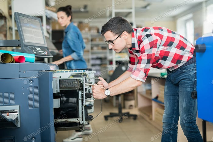 Man in typography working with printer