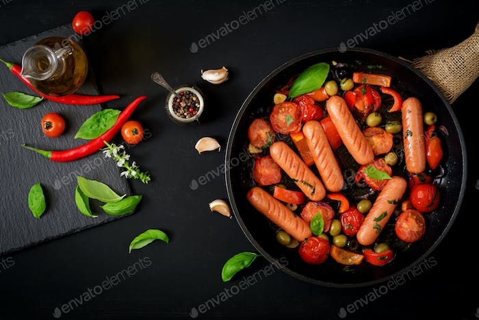 Sausages grilled with vegetables in the Greek style on pan. Flat lay. Top view.