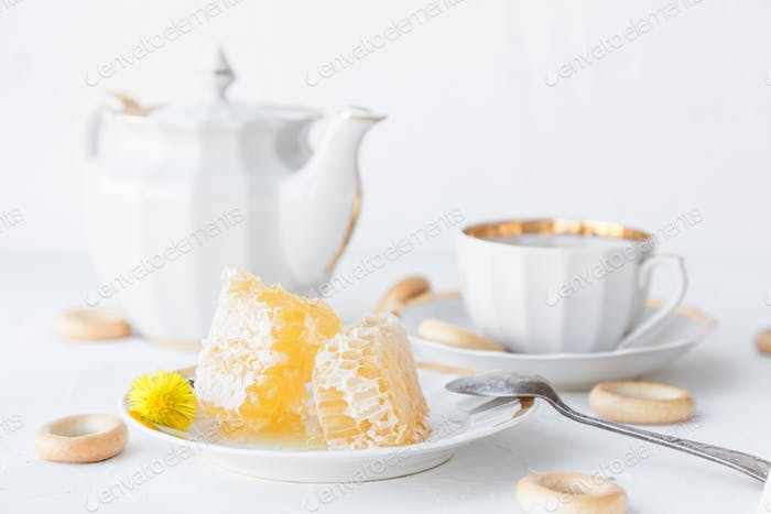 Cup of tea, teapot and honeycomb on a plate, withhoneycomb on background