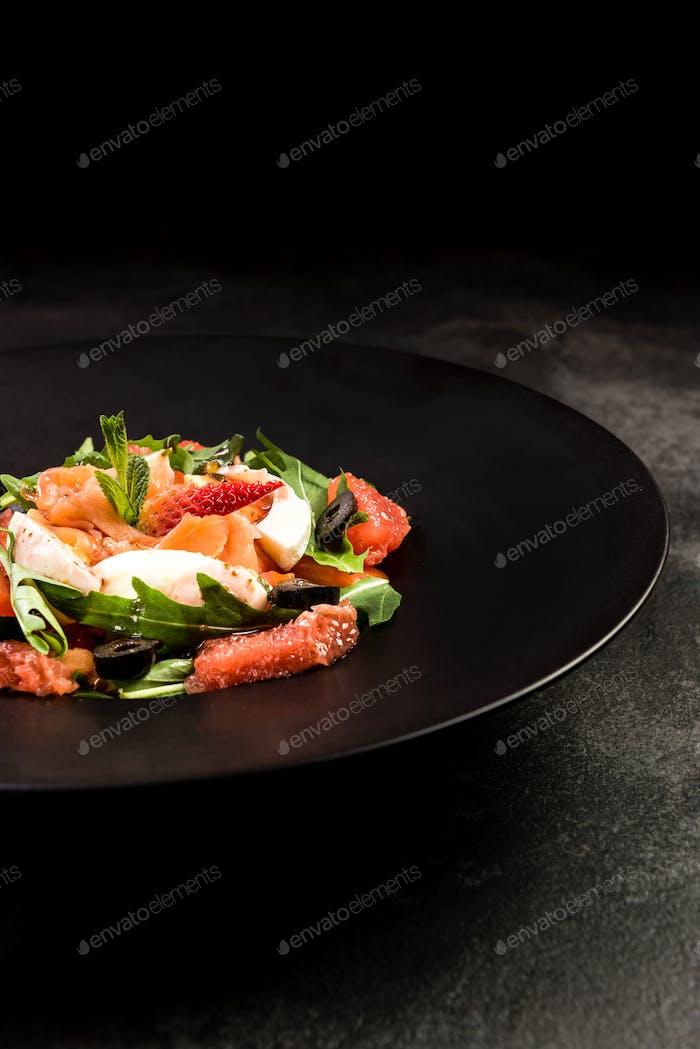 Healthy salad on dark plate.Restaurant dish,healthy eating