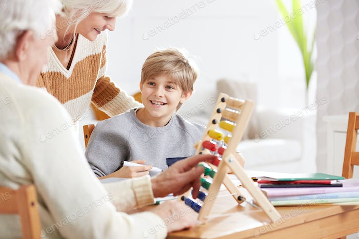Boy studying math with grandparents