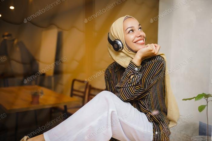 Beautiful arab girl in hijab and headphones