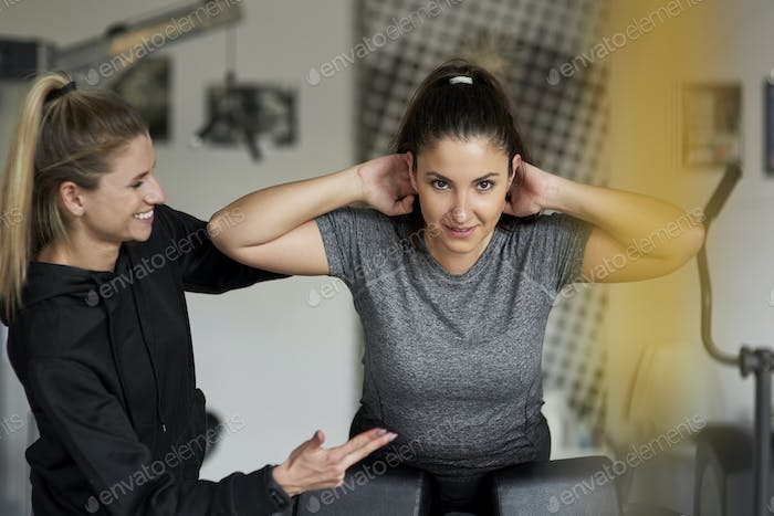 Personal trainer guiding woman at the gym