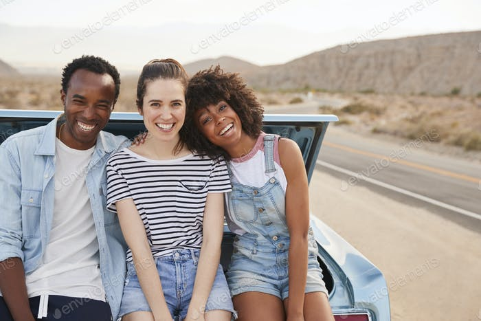 Portrait Of Three Friends Sitting In Trunk Of Classic Car On Road Trip