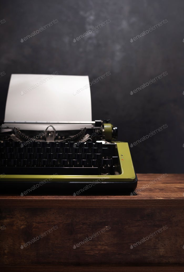 vintage typewriter at wooden table near wall background surface