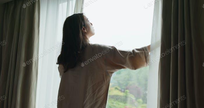 Frau aufwachen am Morgen, öffnen Sie den Vorhang und schauen Sie sich um den Blick außerhalb des Fensters