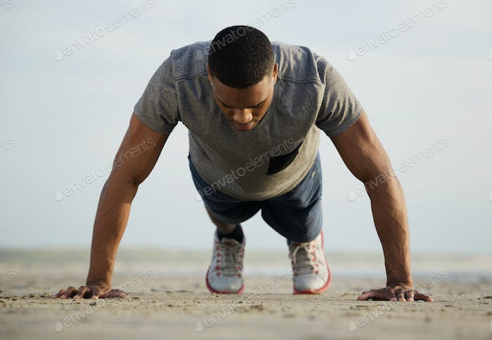 Fit young man doing push ups at the beach