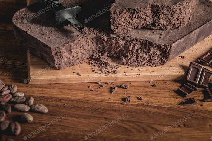 Arrangement of Cocoa beans, nibs and Chocolate bars on wooden su