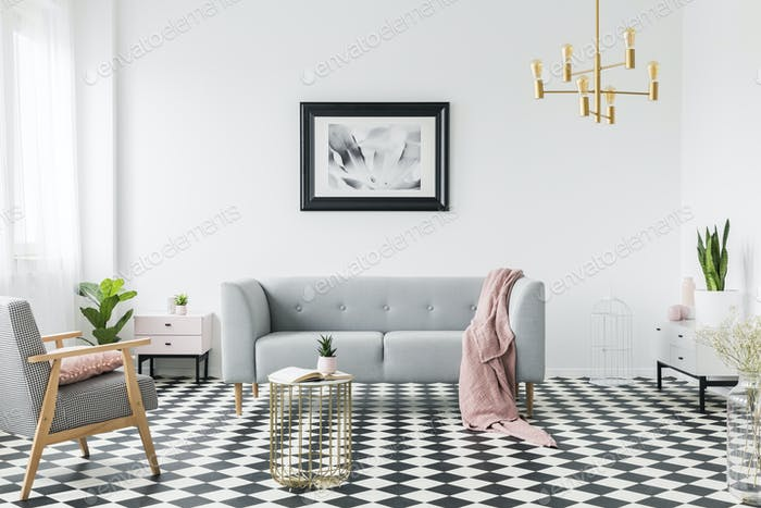 Grey sofa with pink blanket under poster in white flat interior