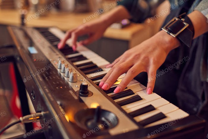 Hands of young female on keys of synthesizer
