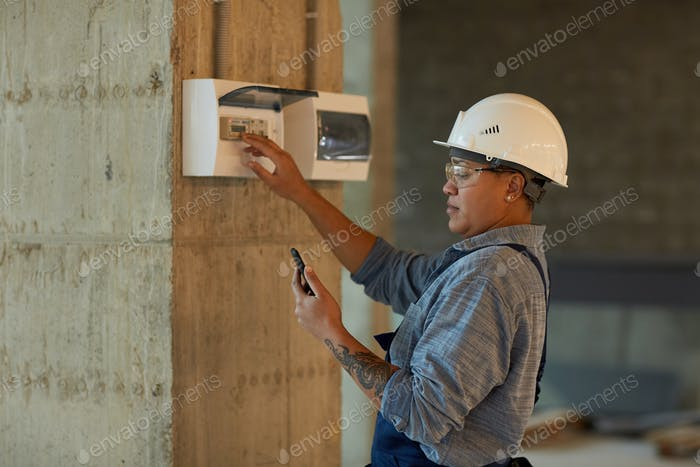 Mixed-Race Female Electrician Inspecting Switchboard