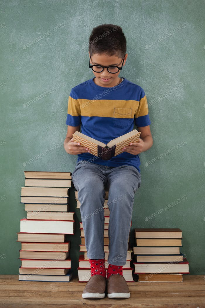 Schoolboy sitting on books stack and reading book