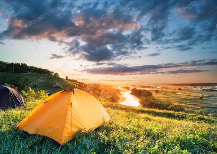 Orange tent on a hill above the river