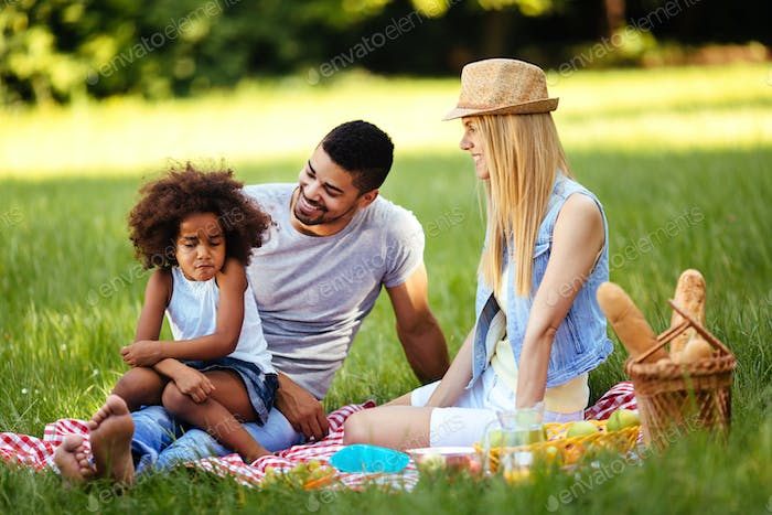 Offended little girl sitting with parents on picnic