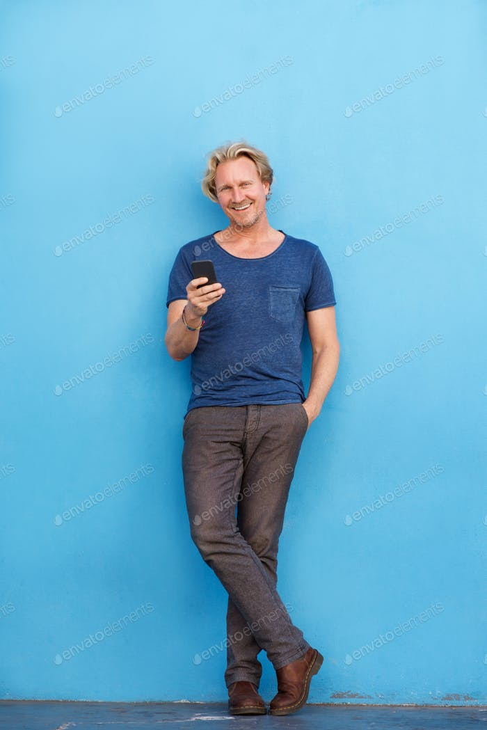 Full body happy man standing by wall with mobile phone