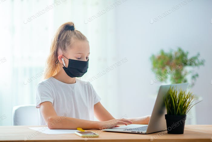 Serious schoolgirl sitting at table with laptop and textbook and doing homework