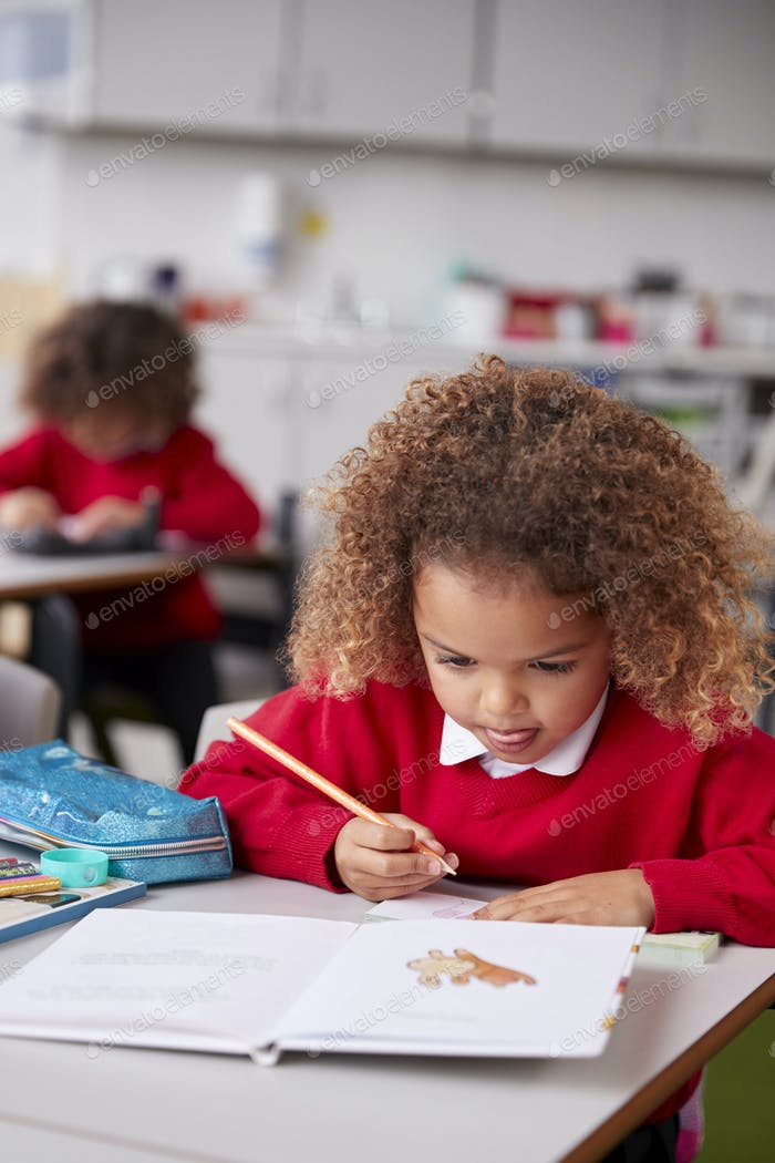 Close up of mixed race schoolgirl sitting at desk in an infant school classroom drawing, vertical