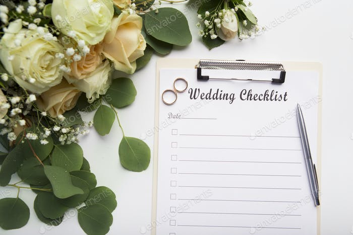 Creative wedding planning checklist with roses and rings