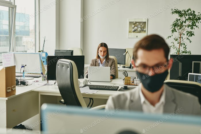 Office woman with mask on chin