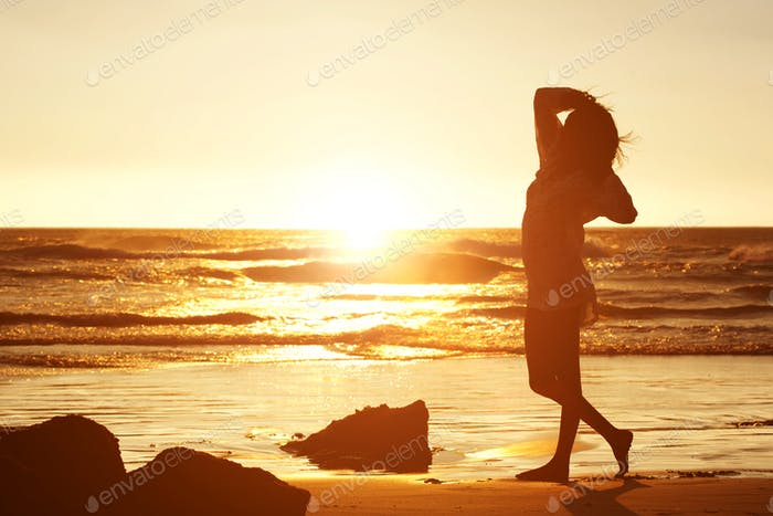 Silhouette of a young woman standing on beach