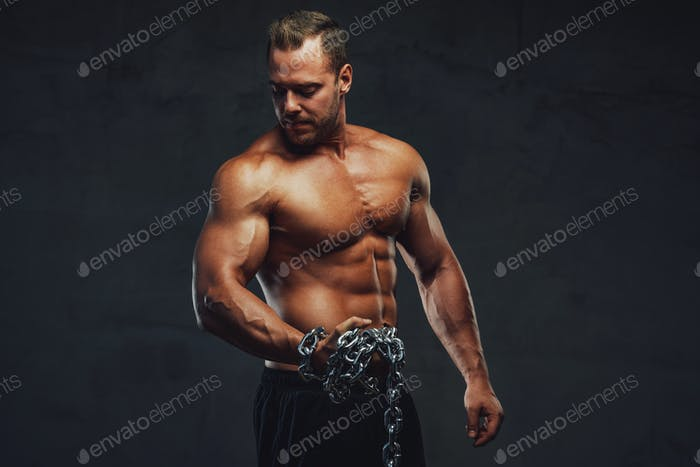 Strong guy with chains posing in special background