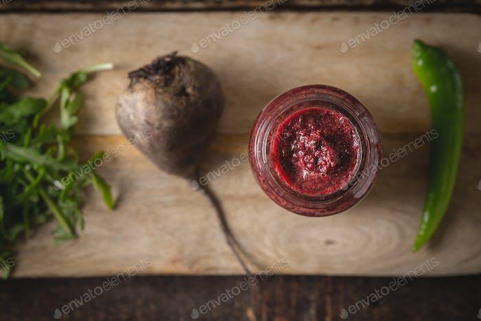 Gemüse-Smoothie mit verschwommenen Zutaten auf der Holzplatte Draufsicht