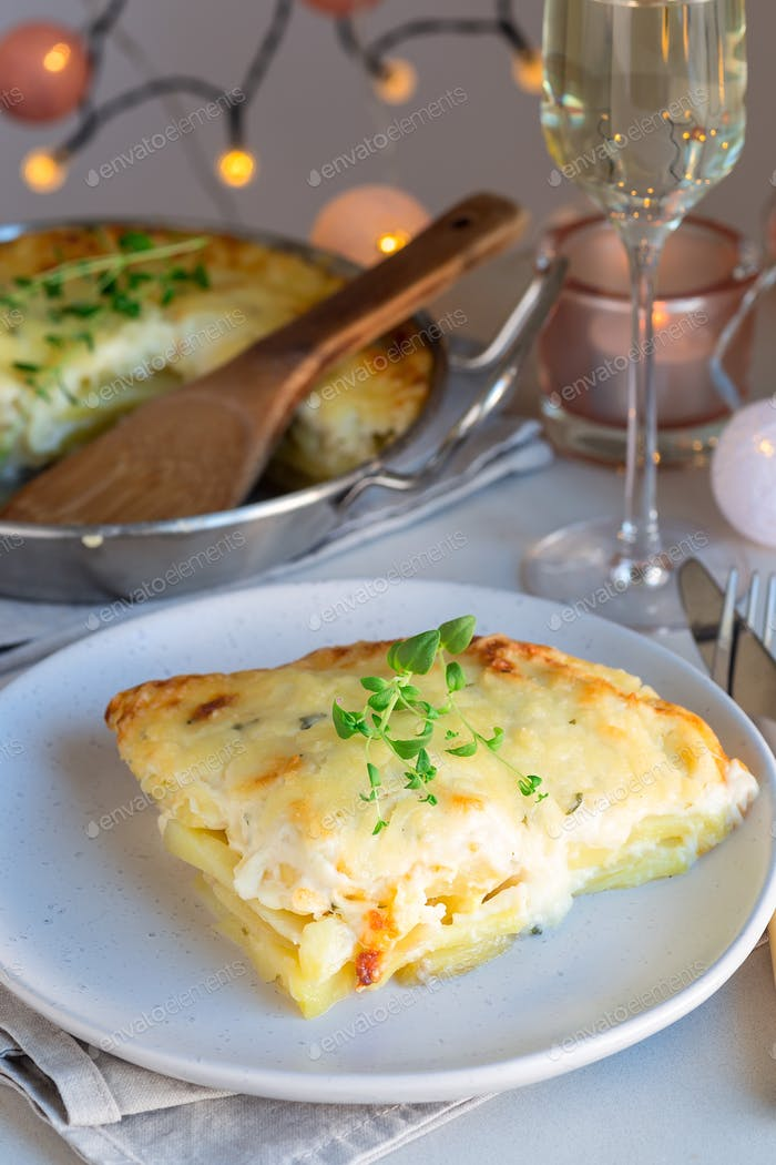 Piece of cheesy scalloped potatoes or potato gratin on a plate,