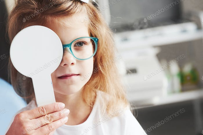 Woman hands holds the occluder. Little girl checking his vision with new green glasses