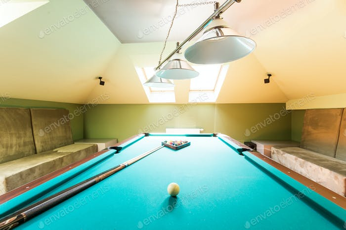 Entertainment attic room with a billiard table
