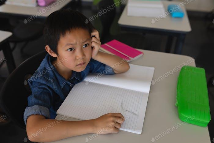 Thoughtful schoolboy looking away in classroom of elementary school