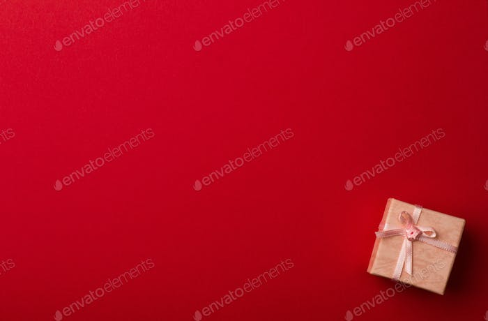 Little pink gift box on red background
