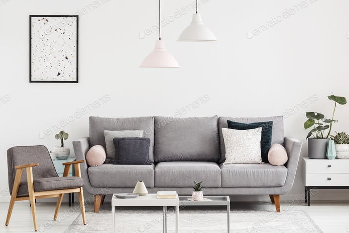 Grey armchair next to settee in white apartment interior with po