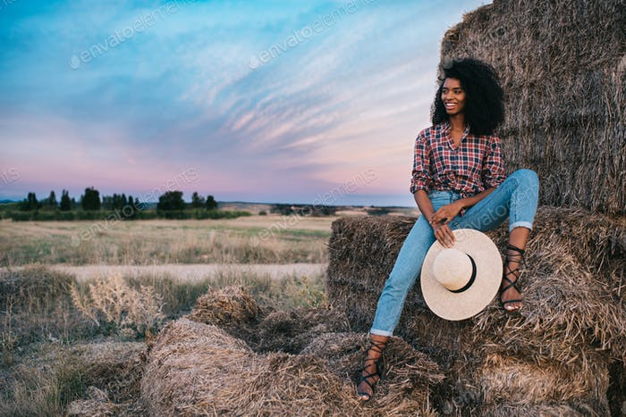 Happy black young woman sitting on a pile of hay