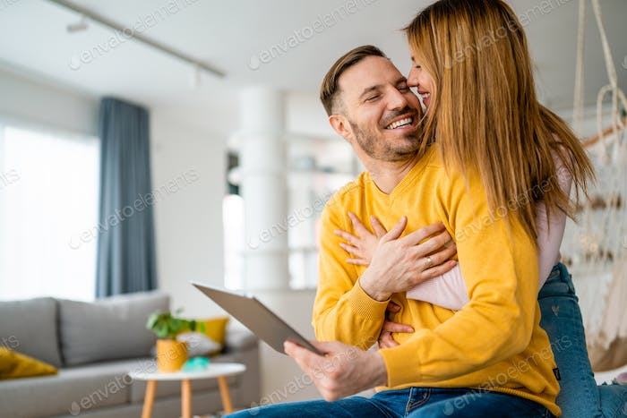 Couple in love using tablet computer at home and having fun