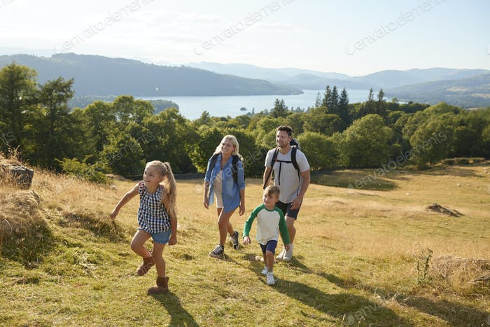 Family Climbing Hill On Hike Through Countryside In Lake District UK Together