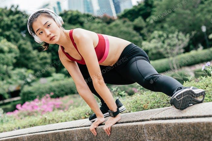 Push yourself. Asian sportswoman exercising outdoors