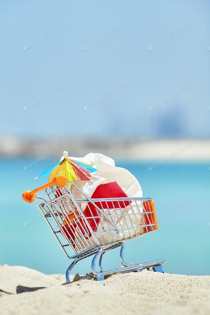 Miniature shopping cart with plastic garbage on a tropical beach