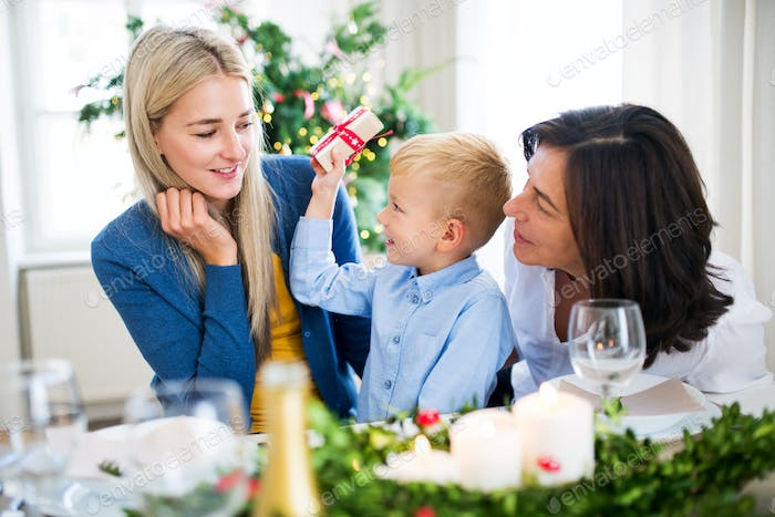 A small boy with present and mother and grandmother at home at Christmas time.