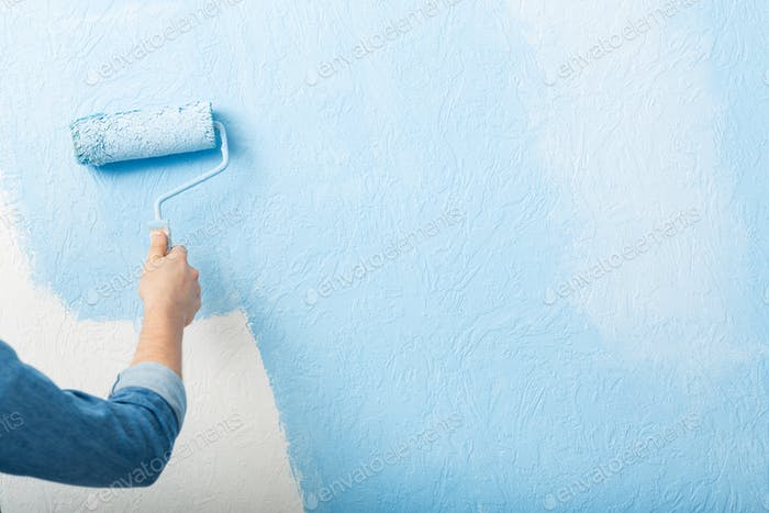 Paints texture wall with roller in blue