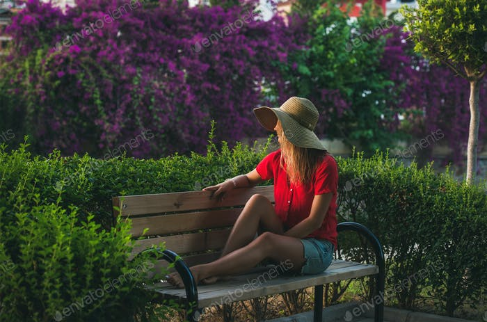 Young woman sitting on bench and looking aside, Alanya, Turkey